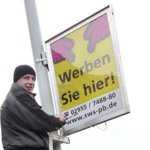 Konstantin Schröder, Mitarbeiter von Städtewerbung Schnelle, bringt einen der Aluminium-Rahmen an, in denen künftig für Veranstaltungen geworben werden darf.© Maaß